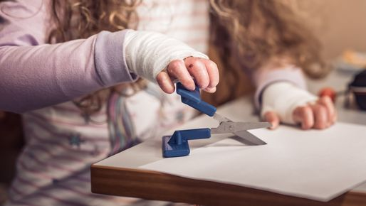 Person living with EB cuts a piece of paper with a pair of adapted scissors
