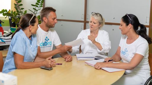 A physician and three nurses during a meeting.