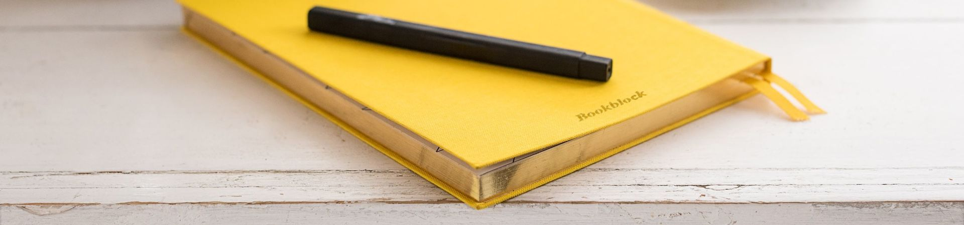 Yellow notebook and black pen lying on a wooden table